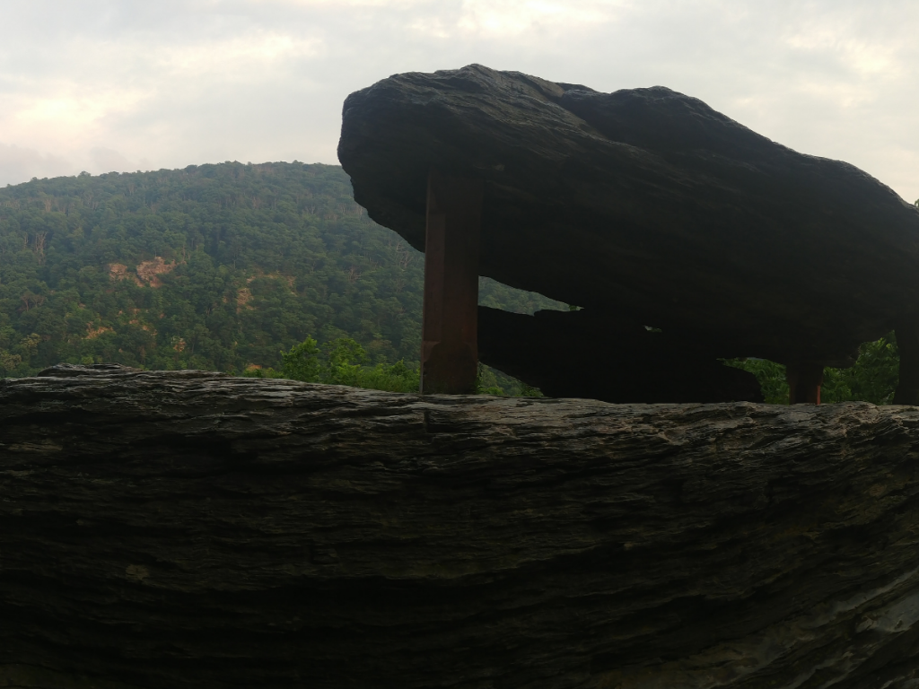Large rock formation with hills in background