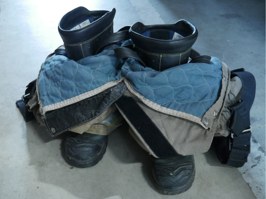 Boots and pants in pile on floor